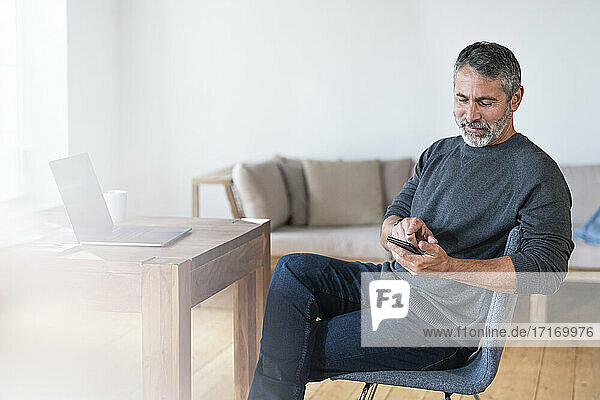 Mature businessman using mobile phone while sitting at home office