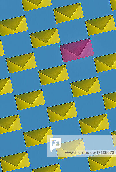 Pattern of rows of yellow envelopes with single pink one