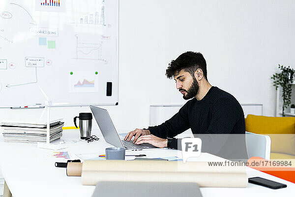 Young businessman using laptop in creative office