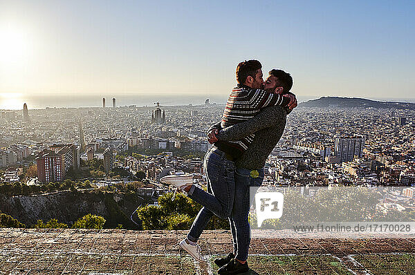 Gay men kissing while standing on viewpoint against cityscape  Bunkers del Carmel  Barcelona  Spain