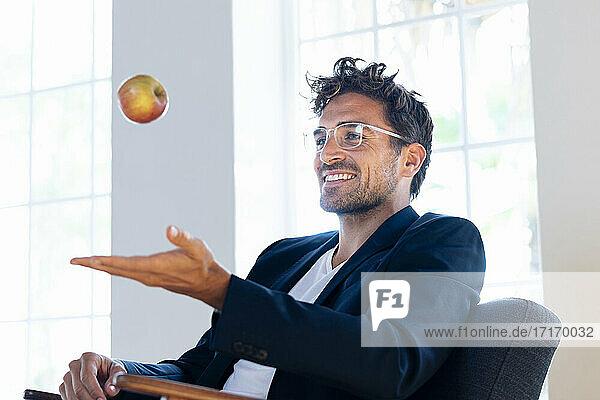 Lächelnder Geschäftsmann  der mit einem Apfel spielt  während er zu Hause sitzt Lächelnder Geschäftsmann, der mit einem Apfel spielt, während er zu Hause sitzt