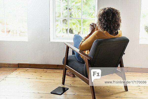 Frau trinkt Tee  während sie zu Hause auf einem Sessel sitzt Frau trinkt Tee, während sie zu Hause auf einem Sessel sitzt