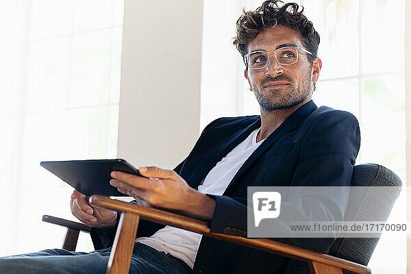 Confident businessman with digital tablet looking away while sitting on armchair at home