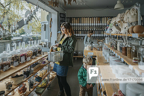 Mature female customer shopping while owner and boy standing in retail store