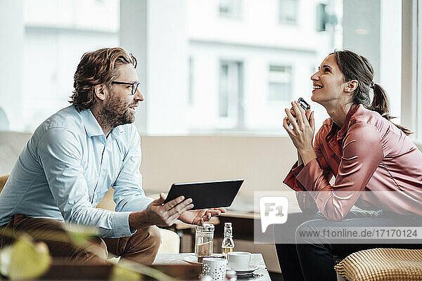 Männliche und weibliche Kollegen lachen beim Diskutieren in einem Café