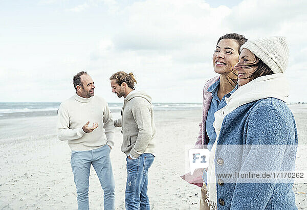 Group of adult friends standing and talking on coastal beach