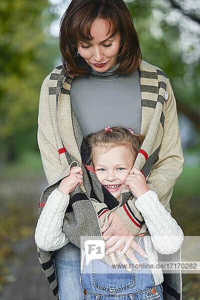 Happy girl hiding in mother's cardigan sweater in park