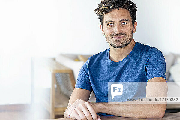 Mittlerer erwachsener Mann mit blauen Augen,  der lächelnd zu Hause sitzt