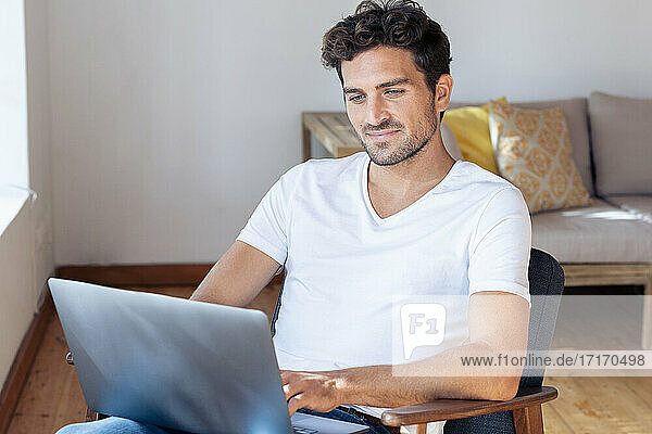 Mid adult man working on laptop while sitting on armchair at home
