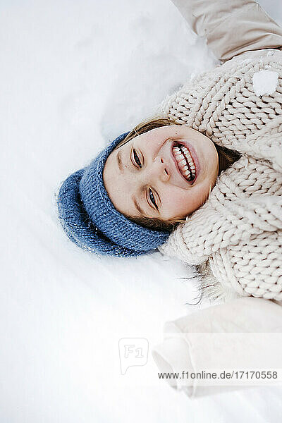 Cheerful girl with scarf lying on snow during winter