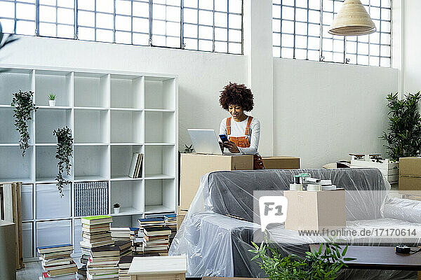 Afro woman using mobile phone by laptop while relocating into new apartment