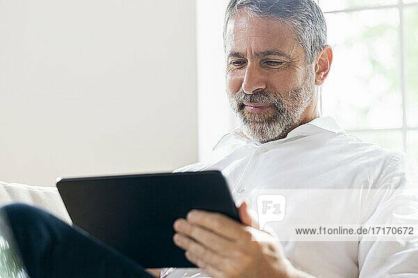 Lächelnder Geschäftsmann  der zu Hause sitzend an einem digitalen Tablet arbeitet Lächelnder Geschäftsmann, der zu Hause sitzend an einem digitalen Tablet arbeitet