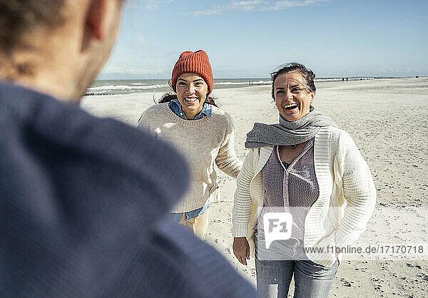 Gruppe von Freunden  die sich am Sandstrand unterhalten und lachen Gruppe von Freunden, die sich am Sandstrand unterhalten und lachen