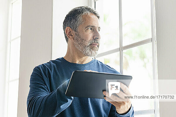 Mature businessman with digital tablet looking away while standing at home