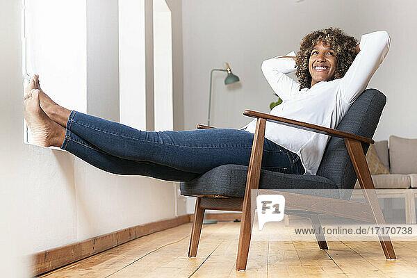 Glückliche Frau lächelt,  während sie sich zu Hause auf einem Sessel ausruht