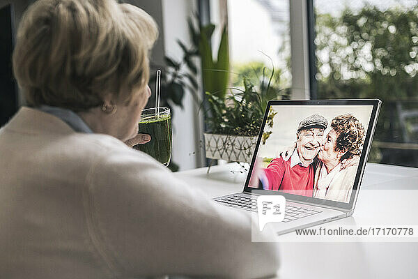 Senior woman on video call with friends through laptop at home