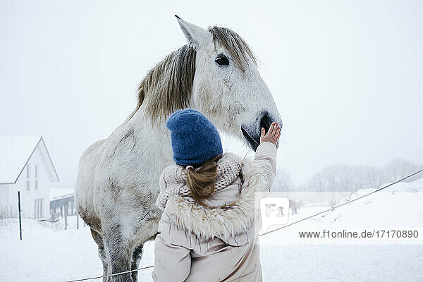 Girl in warm clothing stroking horse on snow during winter