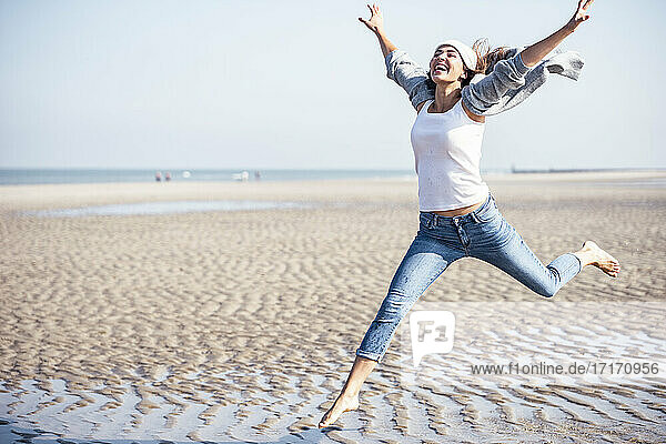 Carefree woman jumping on beach at sunny day