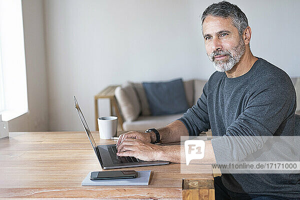 Businessman with laptop looking away while sitting at home office