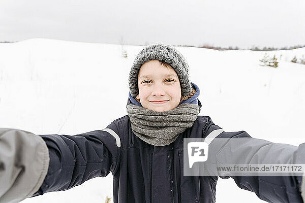 Smiling boy standing on snow covered landscape against sky