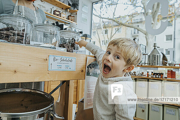 Excited little boy pointing at chocolate jar in candy shop