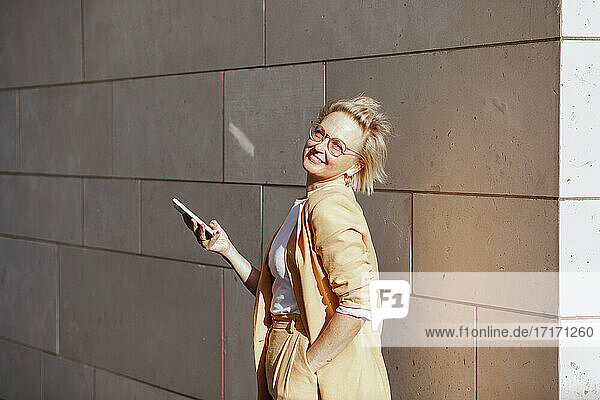 Smiling female entrepreneur with smart phone standing against wall