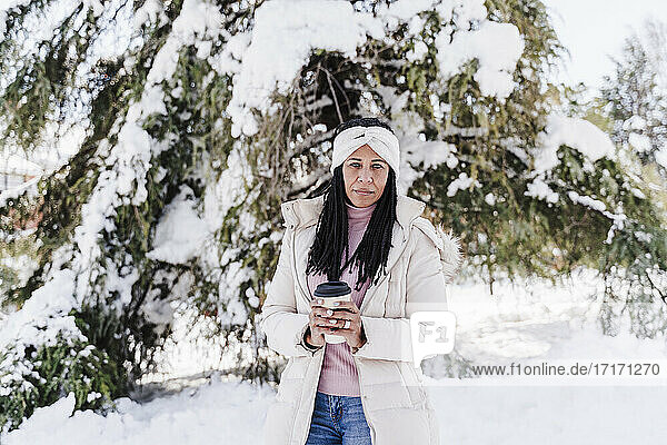 Mature woman with coffee cup in park during winter season