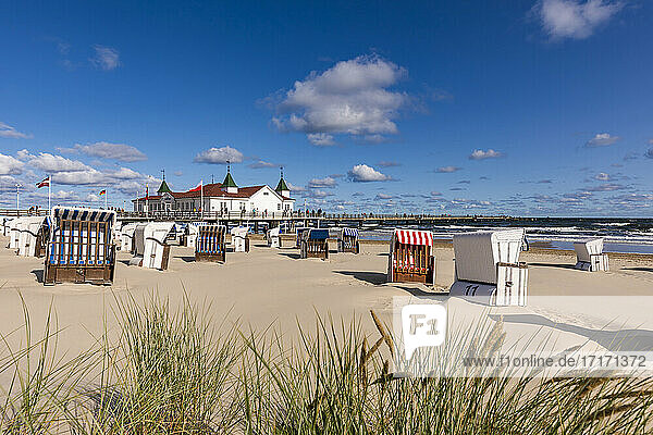 Germany  Mecklenburg-Western Pomerania  Heringsdorf  Hooded beach chairs on empty beach with Ahlbeck Pier in background