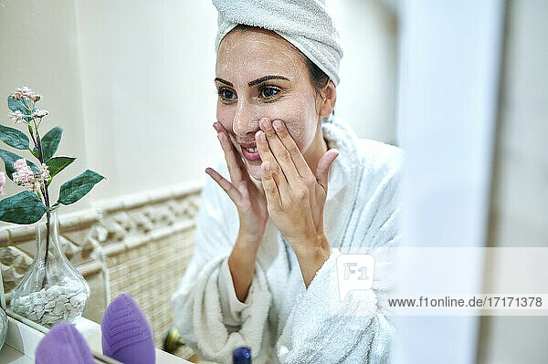 Reflection of smiling woman applying face cream in bathroom