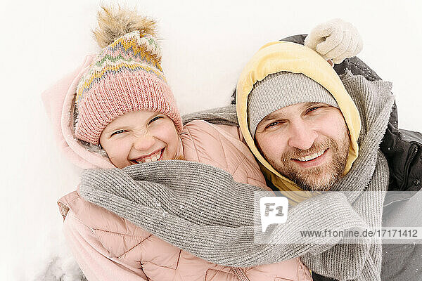 Close-up of cheerful father and daughter lying on snowy land