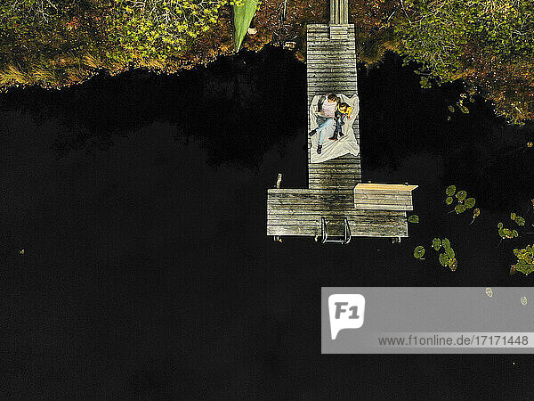 Aerial view of mother and daughter sitting on pier over lake in forest