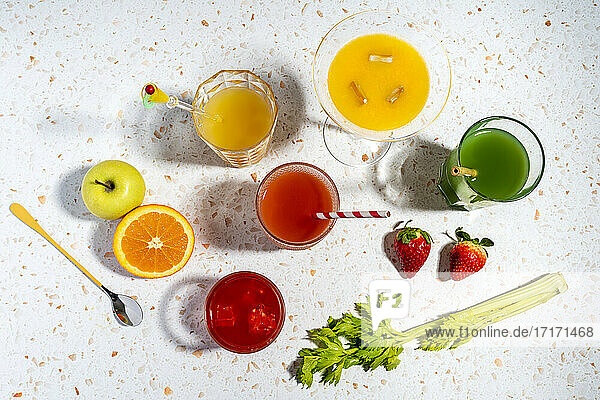Multi colored healthy fruit cocktail glasses kept on modern terrazzo marble