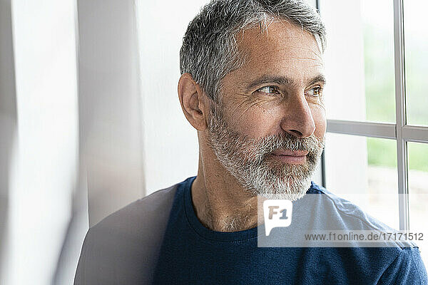 Smiling man looking through window while standing at home