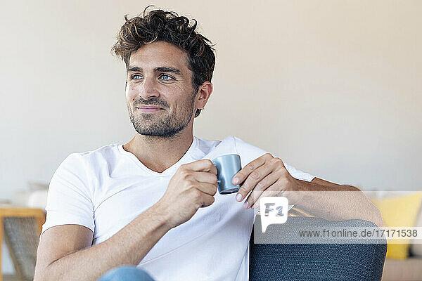 Lächelnder Mann trinkt Kaffee und sitzt auf einem Stuhl zu Hause Lächelnder Mann trinkt Kaffee und sitzt auf einem Stuhl zu Hause