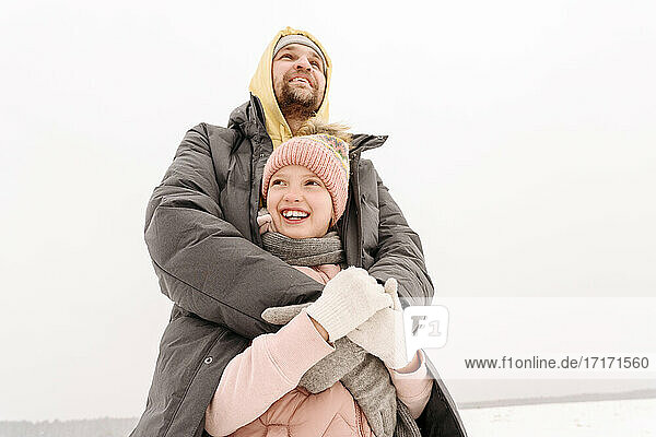 Smiling father covering daughter in winter coat while looking away against clear sky