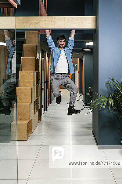 Happy male professional hanging at doorway in office