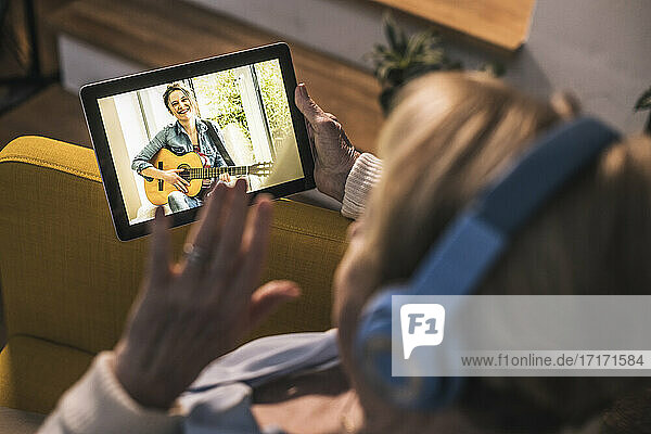 Mother waving to daughter on video call through digital tablet in living room