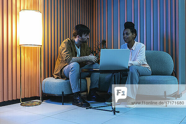 Male and female colleagues with laptop planning while sitting in illuminated work place
