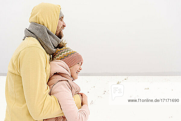 Father embracing daughter while standing on snowy landscape against clear sky