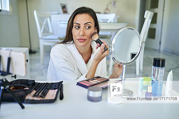 Female influencer applying make-up while vlogging on smart phone at home