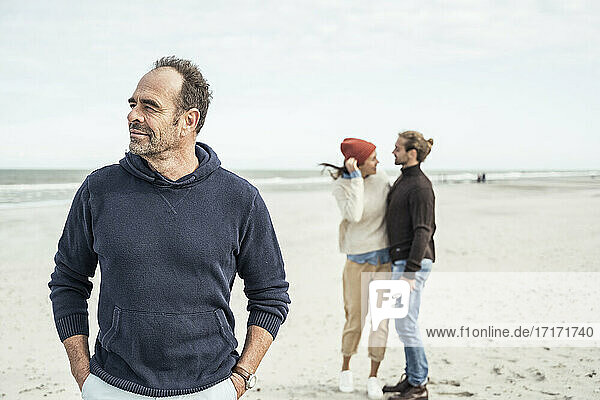 Portrait of man standing on sandy beach with young couple in background