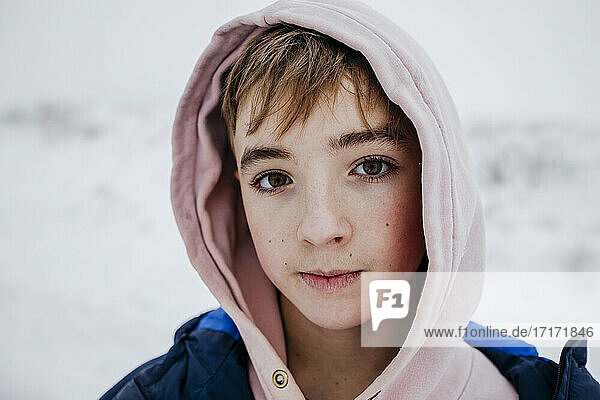 Teenage boy with brown eyes in warm clothing on snow