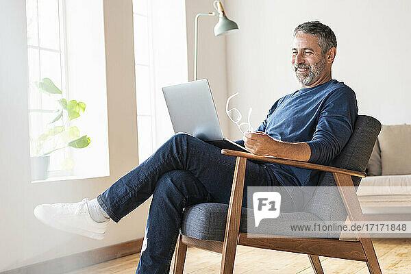Lächelnder Geschäftsmann  der einen Laptop benutzt  während er zu Hause auf einem Sessel sitzt Lächelnder Geschäftsmann, der einen Laptop benutzt, während er zu Hause auf einem Sessel sitzt
