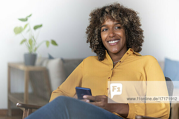 Mid adult woman with mobile phone looking away while sitting at home