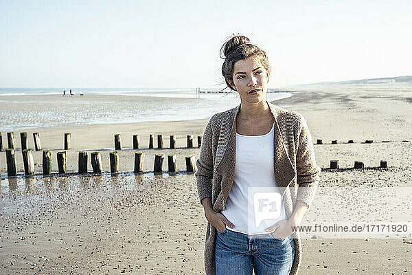 Junge Frau mit Händen in den Hosentaschen schaut weg auf den Strand Junge Frau mit Händen in den Hosentaschen schaut weg auf den Strand