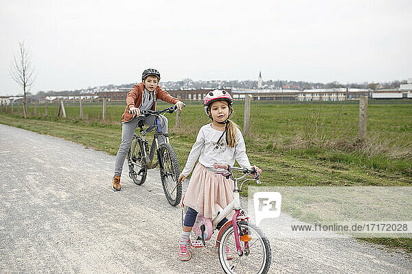 Brother and sister with bicycles on road against clear sky