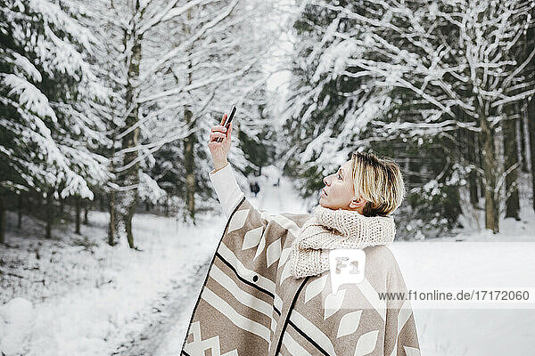 Mature woman in warm clothing taking selfie through smart phone in snow