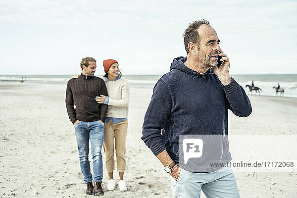 Portrait of man standing on sandy beach and talking on smart phone with young couple in background