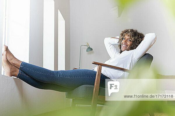 Lächelnde Frau mit Händen hinter dem Kopf  die sich auf einem Sessel zu Hause entspannt Lächelnde Frau mit Händen hinter dem Kopf, die sich auf einem Sessel zu Hause entspannt