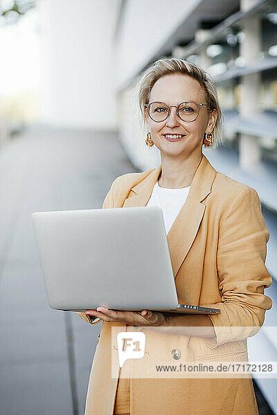 Smiling blond female professional holding laptop